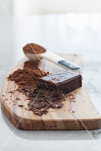 Dark chocolate and cocoa powder on a wooden chopping board