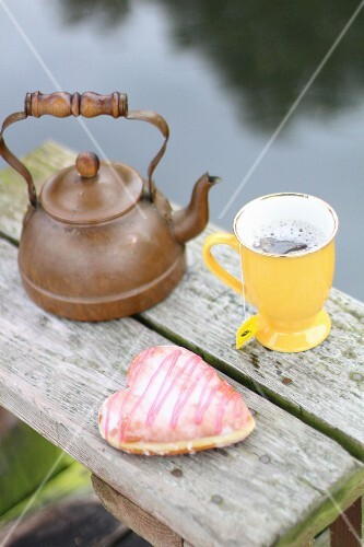 A cup of tea and a heart-shaped doughnut on the bank of a lake