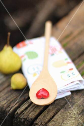 A wooden spoon with a heart and two small pears