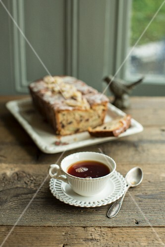 A cup of Earl Grey tea and pear cake with candied ginger and chocolate