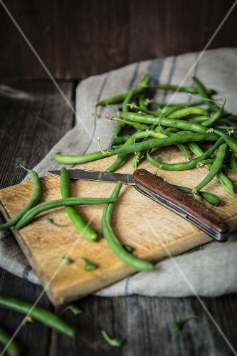 Green beans on a chopping board with a folding knife