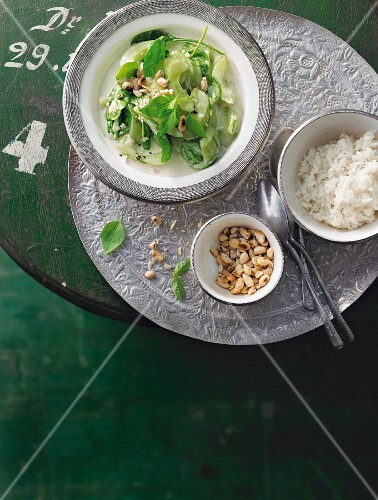 Braised cucumber and coconut curry with spinach, peanuts and rice