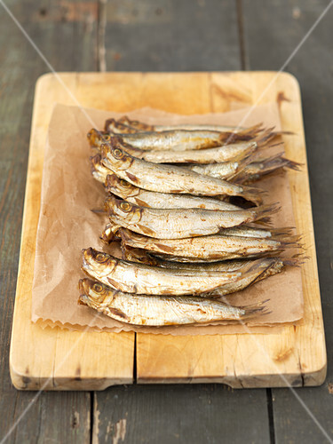 Smoked sprats on a chopping board