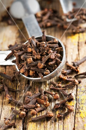 Cloves, some in a measuring spoon