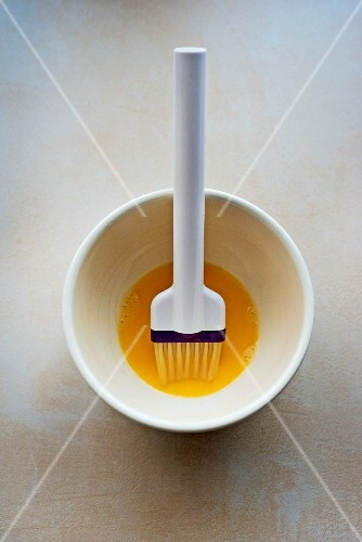 A bowl of beaten egg yolk and a baking brush