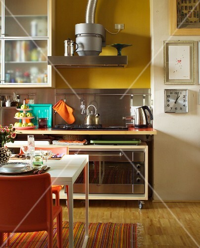 Kitchen-dining room with floating worksurface over base cabinet on castors; set dining table and orange chairs in foreground