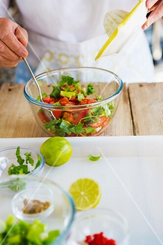 Tomato salad with lemon dressing being made