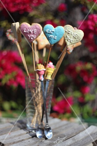 Heart-shaped biscuits on sticks with iced writing