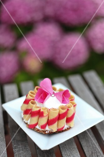 A mini cake decorated with wafer rolls