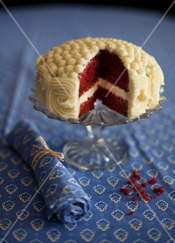 A red velvet cake decorated with buttercream, sliced