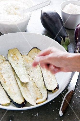 Aubergine slices being sprinkled with salt
