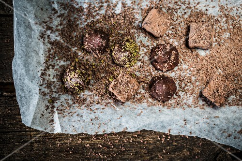 Various homemade chocolate pralines with grated chocolate and tissue paper