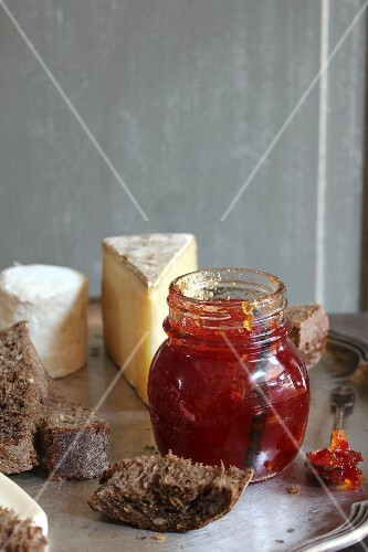 A jar of chilli and apple jam, bread and cheese