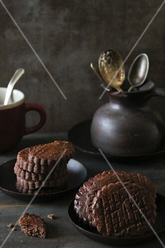 A stack of chocolate biscuits and a jug of cutlery