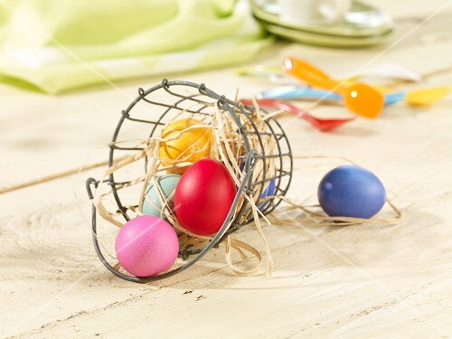 Colourful Easter eggs in a wire basket with straw