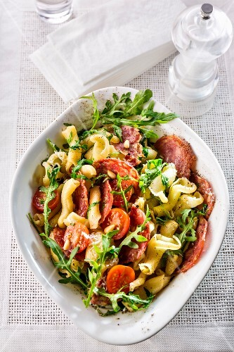A pasta salad with tomatoes, salami and rocket (seen from above)
