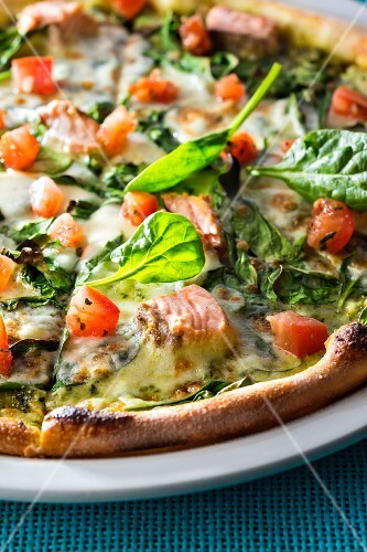 Pizza with salmon, spinach and tomato