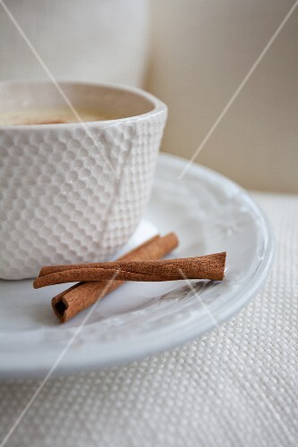 A cup of eggnog with cinnamon sticks