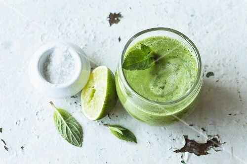 Green spinach smoothie with herbs, cucumber, avocado and celery