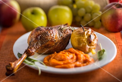 Goose leg with pumpkin puree and a baked apple
