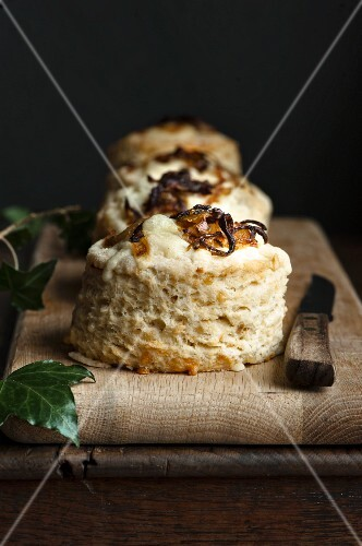 Cheese and onion scones on a wooden chopping board with a knife