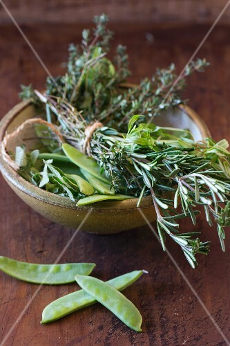Mange tout and a bunch of herbs in a ceramic bowl