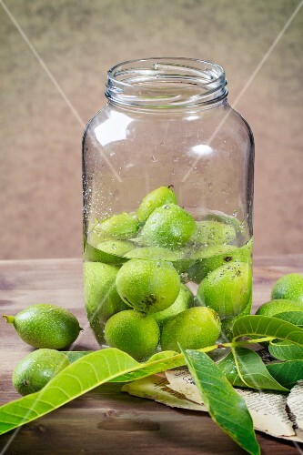 Young green walnuts in a glass jar for making jam