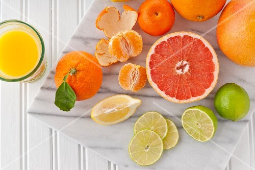 Various citrus fruit and a glass of orange juice