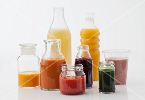 Various juices and smoothies in bottles and glasses