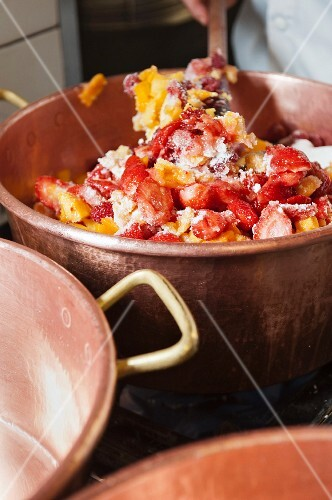 Mangos, raspberries and strawberries being stirred in a copper pot for making jam