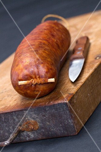 Saucisse De Morteau (French sausage) on a chopping board with a knife