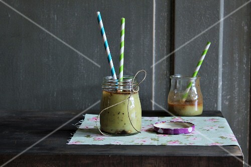 Kiwi smoothies in jars with straws