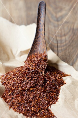 Rooibos tea leaves on a wooden spoon and on paper