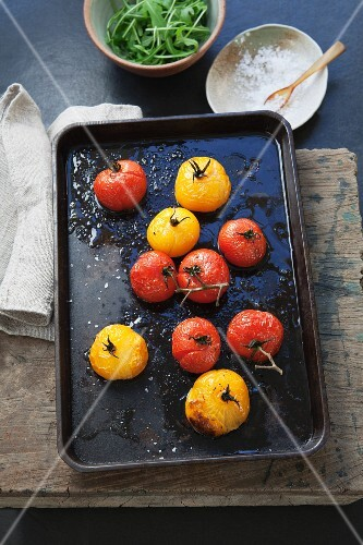 Oven-roasted red and yellow tomatoes on a baking tray
