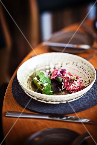 Raw wagyu beef shoulder with enoki mushroms, wasabi leaves and chillis