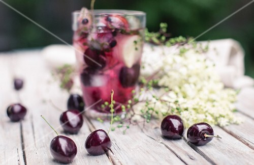 Ice cubes with cherries in a glass of juice