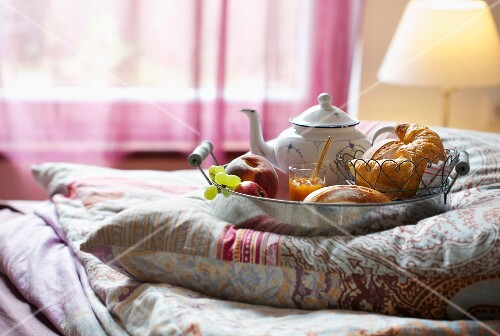 A breakfast tray on a cushion on a bed