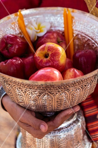 A hand holding a bowl of apples as a sacrifice in a Buddhist temple (Vientiane, Laos)