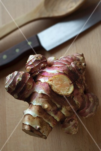 A Jerusalem artichoke on a chopping board with a knife and a wooden spoon