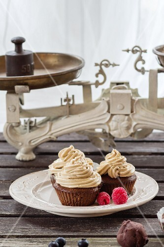 Chocolate cupcakes with butter cream and fresh berries on an old wooden table in front of a window