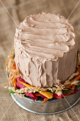 An autumnal chocolate pumpkin layer cake on a rustic cake stand with autumn leaves
