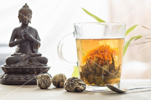 A glass of floral tea, closed flowers and a Buddha figure