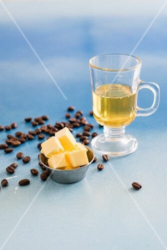 Oil in a glass with diced butter and coffee beans