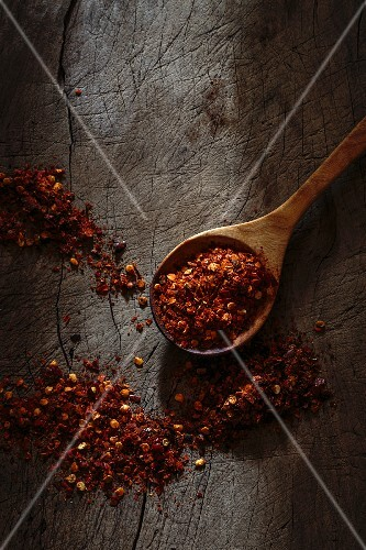 Dried chilli flakes on a wooden spoon and on a wooden surface