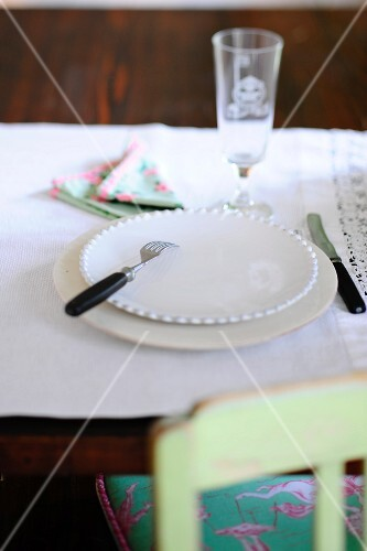 A place setting on a rustic table with a white tablecloth