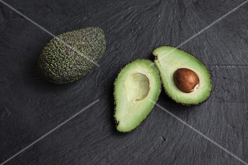 Avocados, whole and halved, on a slate platter