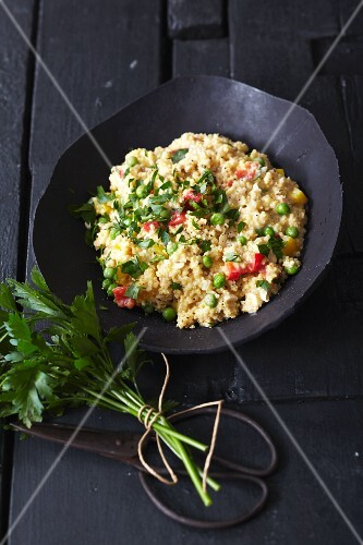 Vegetarian millet risotto with peppers, peas, ajvar and parsley