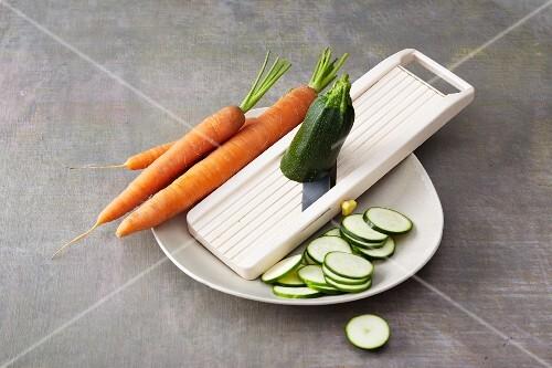 A vegetable grater with carrots and courgettes