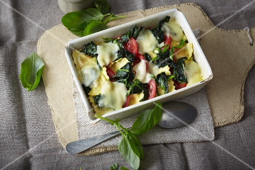 Gratinated ravioli with tomatoes, spinach and mozzarella