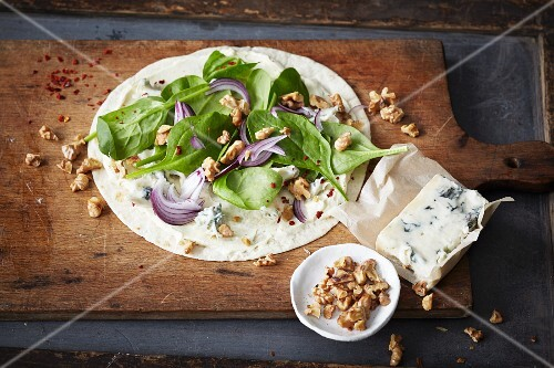 A wholemeal wrap with red onions, baby spinach, Gorgonzola and walnuts